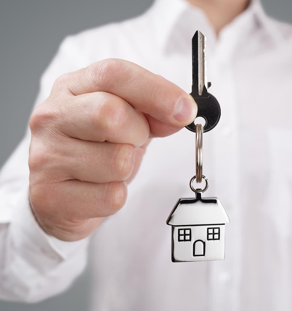 Man holding out house key on a house shaped keychain