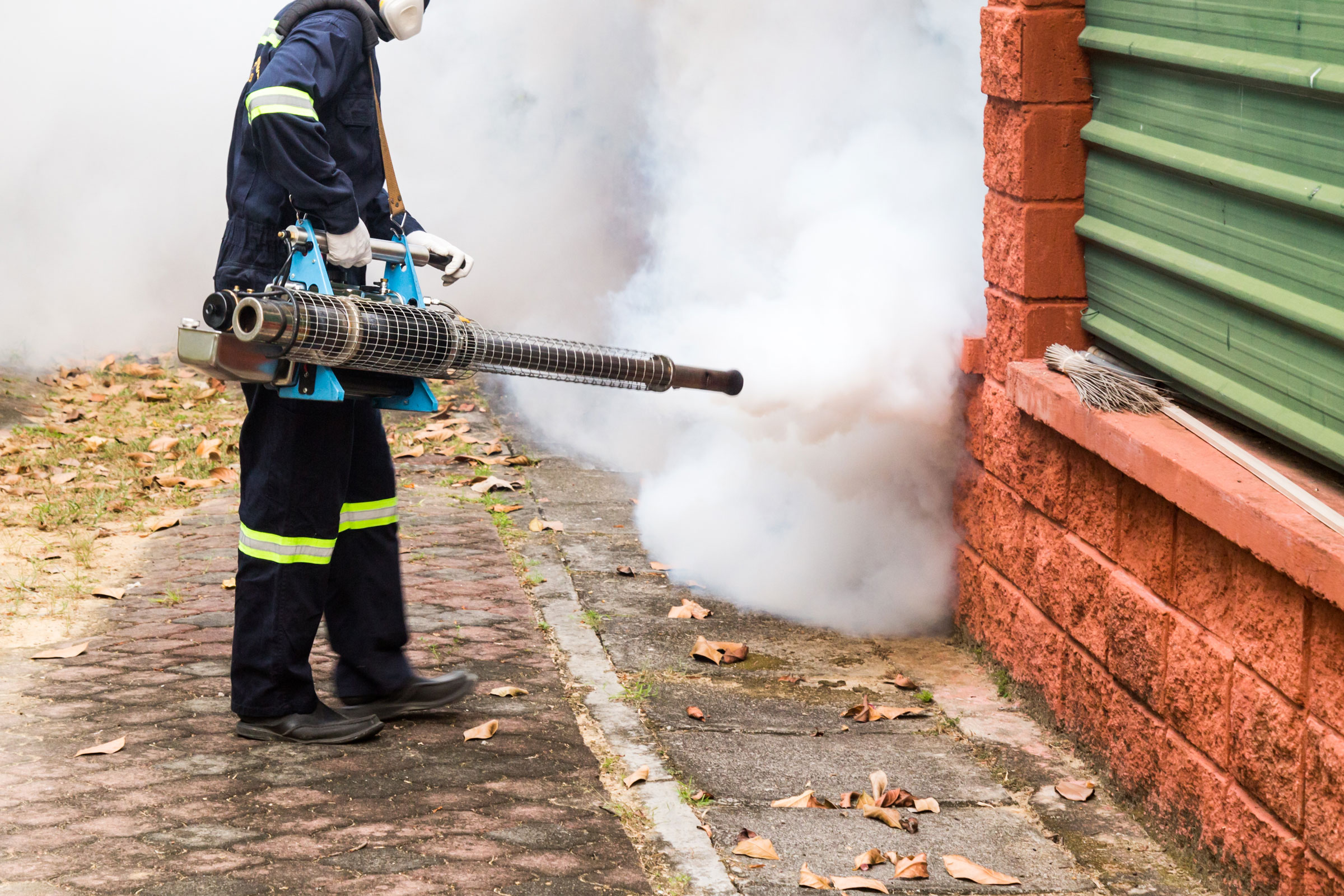 worker-fogging-residential-area-with-insecticides-PCMFT9M